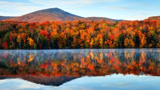 A tranquil lake in Vermont with autumn leaves and a mountain in the background
