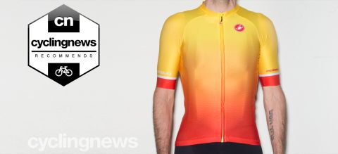 Writer wearing yellow and orange Castelli Aero Race 6.0 jersey, standing in front of blank grey background. Image is overlaid with 'recommends' badge