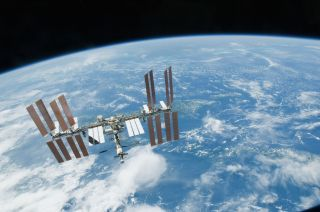 The International Space Station flies above Earth in 2010. Two crewmembers will launch to the orbiting outpost on a one-year mission in March 2015.