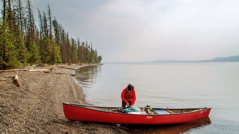 Best canoe backpack 2018: a man fills his red canoe with supplies