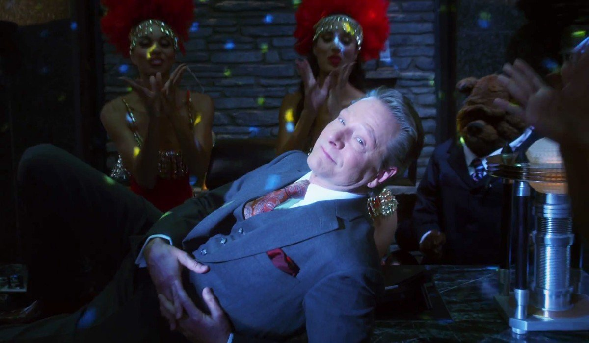 The Muppets Chris Cooper leans on his desk in musical fashion
