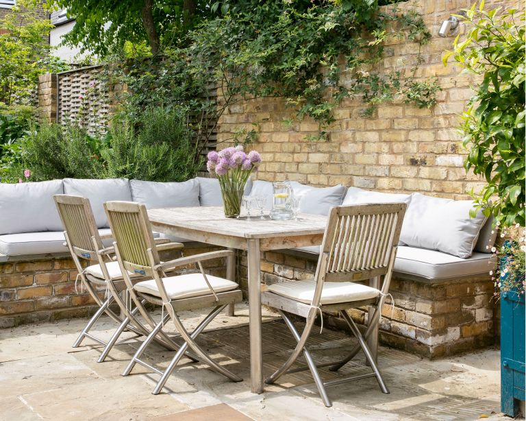Patio costs illustrated in a walled garden with wooden table, chairs and bench seating to show the cost of laying a patio.
