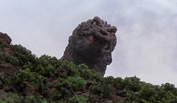 Godzilla, Mothra, King Ghidorah: Giant Monsters All-Out Attack Godzilla peers over a hill, sneering