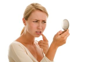A woman looks for a cold sore in a mirror.
