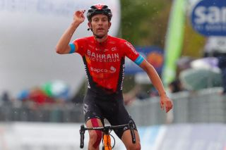 TOPSHOT Team Bahrain rider Switzerlands Gino Mader celebrates as he crosses the finish line to win during the sixth stage of the Giro dItalia 2021 cycling race 160 km between Grotte di Frasassi and Ascoli Piceno San Giacomo on May 13 2021 Photo by Luca Bettini AFP Photo by LUCA BETTINIAFP via Getty Images