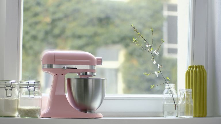 Pink Guava KicthenAid mixer sitting on a windowsill