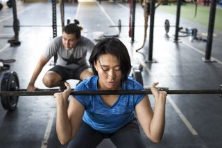 Woman and man weight lifting