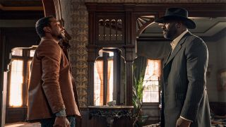 Jonathan Majors and Idris Elba stand face-to-face as Nat Love and Rufus Buck in The Harder They Fall
