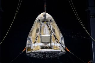 SpaceX's Crew Dragon Resilience is lifted onto its recovery ship in the Gulf of Mexico, off the coast of Panama City, Florida on Sunday, May 2, 2021. The panels covering the capsule's parachutes were ejected in flight and splashed down separately.