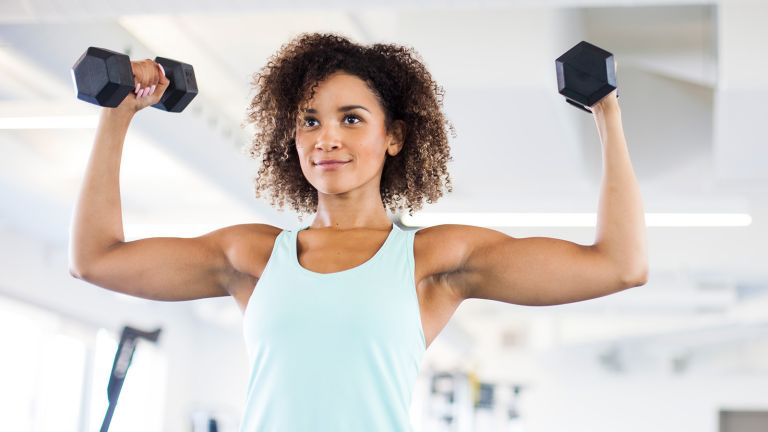 A woman with strong arms doing a dumbbell arms workout