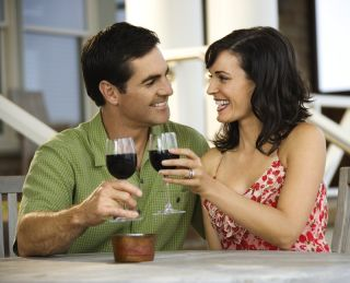 A couple toast with glasses of red wine.