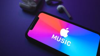 the apple music app on a smartphone next to some airpods