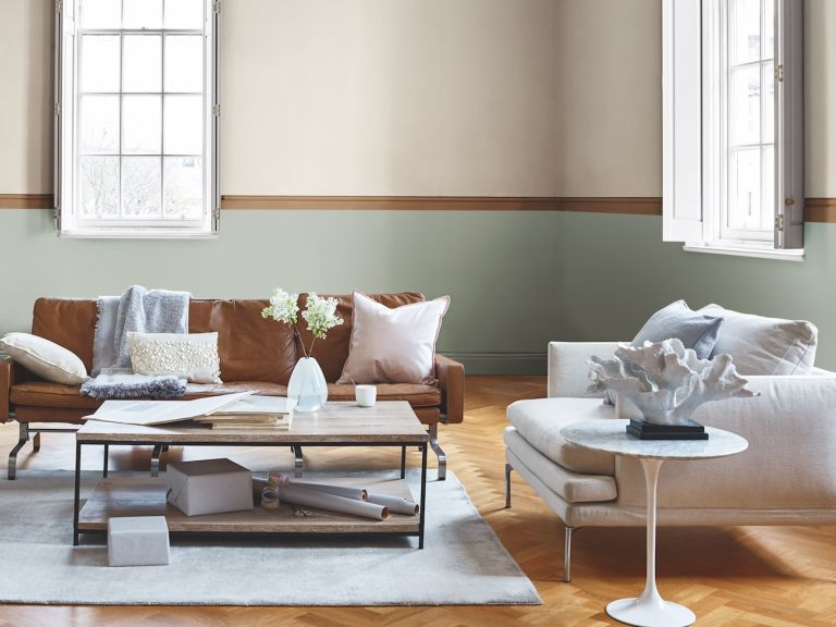 bright living room with a painted stripe, brown leather sofa and wooden coffee table