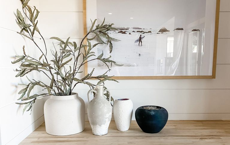 DIY ceramic vases on table with olive branches, more pots and a frame