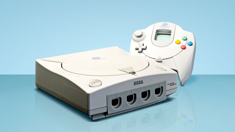 Sega Dreamcast console with controller, on blue background