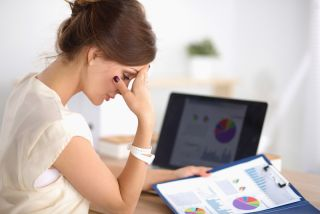 A woman sits in her office, looking stressed out.