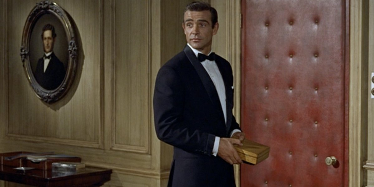 Dr No Sean Connery stands in a tuxedo holding a box