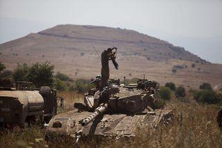 An Israeli soldier stands on a Merkava tank on the Israeli-Syrian border near Quneitra on June 22, 2014.