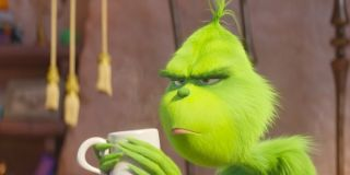 The Grinch has a cup of coffee with a scowl on his face