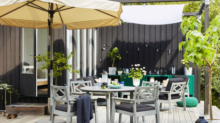 decked terrace with dining set, parasol and seating area with a sail shade