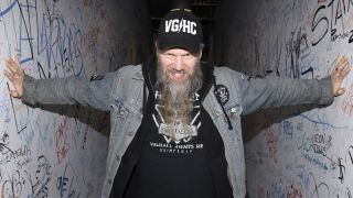 Johan Hegg of Amon Amarth standing with his arms outstretch, touching graffiti-covered walls