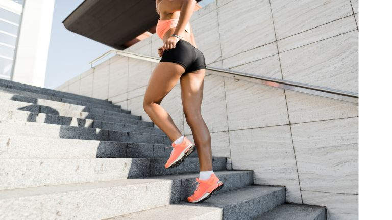 Woman running up a flight of stairs outdoors