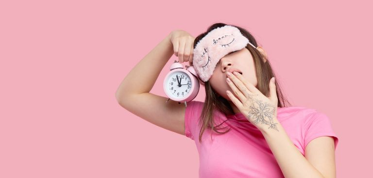 best sleep aid - Close-up of yawning woman with sleep mask and alarm clock against pink background