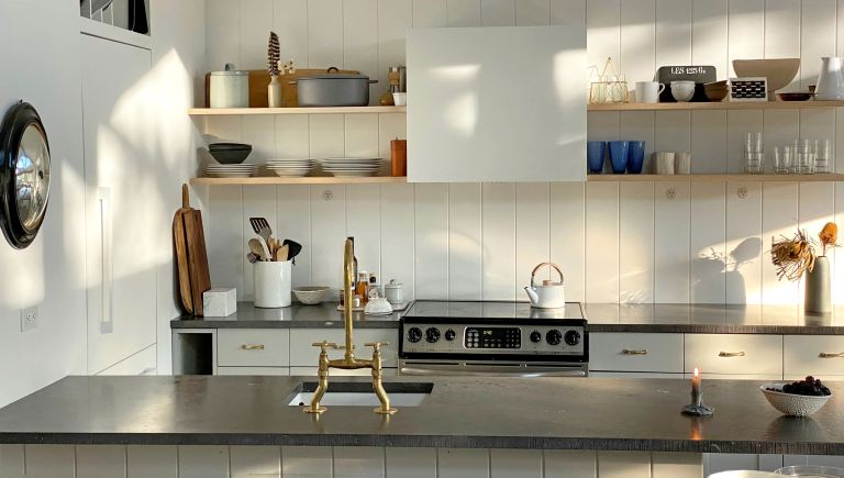 Jenna Lyons' beach house kitchen with black surfaces and white paint