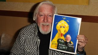 "Puppeteer Caroll Spinney holds a photograph of himself and two ""Sesame Street"" puppets he controlled in 2012."