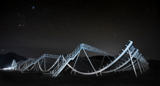 A photo shows the Canadian Hydrogen Intensity Mapping Experiment Fast Radio Burst Project at night.