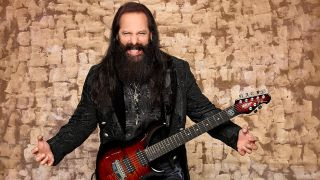 John Petrucci standing next to a wall with a guitar