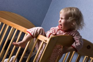 toddler in crib having a temper tantrum