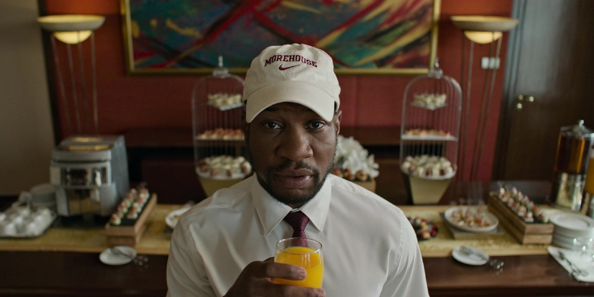 Da 5 Bloods Jonathan Majors holding an orange juice in front of the hotel buffet