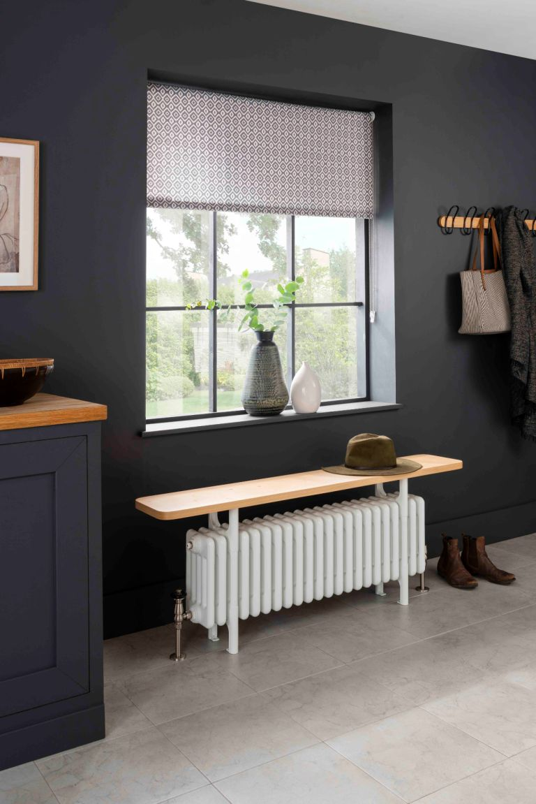 black hallway with radiator with bench on top, peg rail, stone floor and sideboard