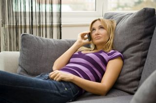 A woman sits on a couch, talking on the phone.