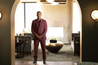Solos: Tom, played by Anthony Mackie, stands in a burgundy suit in a slick, chrome-filled living room, looking pensive