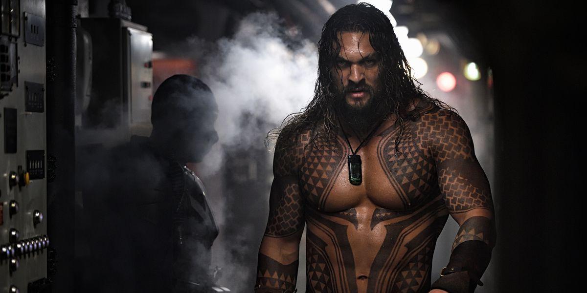 Aquaman walks toward the camera as steam billows behind him