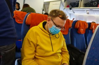 It may be a good idea to wear a face mask in a crowded place, such as an airplane, during the COVID-19 outbreak.