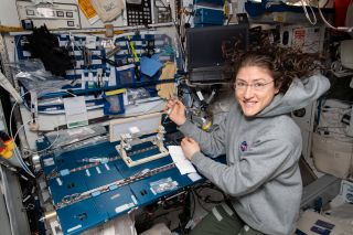 NASA astronaut Christina Koch monitors a space-station experiment called Capillary Structures.