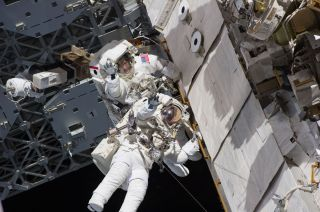 Astronauts Steve Bowen and Alvin Drew wave during the first spacewalk of their STS-133 mission on Feb. 28, 2011