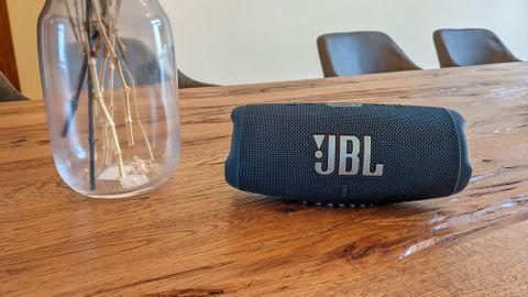 JBL Charge 5 Bluetooth Lautsprecher auf einem Holztisch neben einer Blumenvase