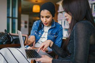 Mujeres mirando un Macbook