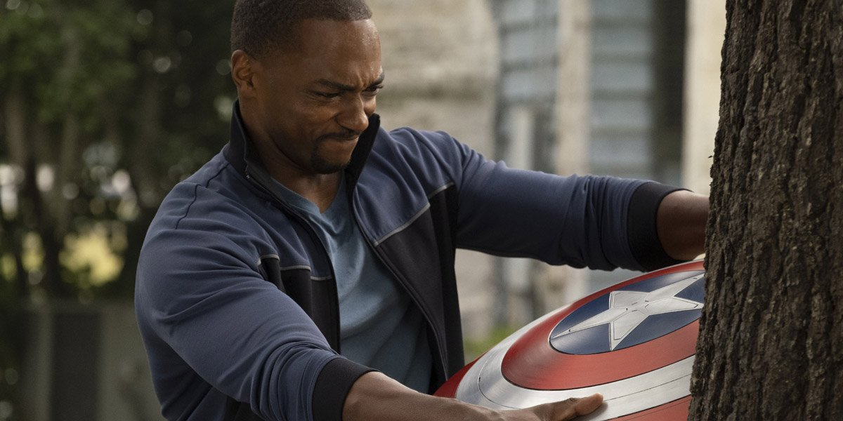 Sam Wilson/Falcon (Anthony Mackie) pulling Captain America's shield out of a tree in The Falcon And The Winter Soldier