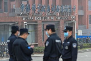 Security personnel stand guard outside the Wuhan Institute of Virology in Wuhan as members of the World Health Organization (WHO) team investigating the origins of the COVID-19 coronavirus make a visit to the institute on February 3, 2021.