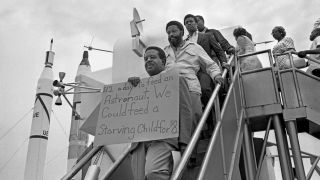 Reverend Ralph Abernathy holds a sign protesting poverty in the U.S. at the Apollo 11 launch.