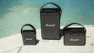 Three portable Marshall speakers next to a swimming pool