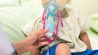 A young boy inhaling medication with inhalation mask.