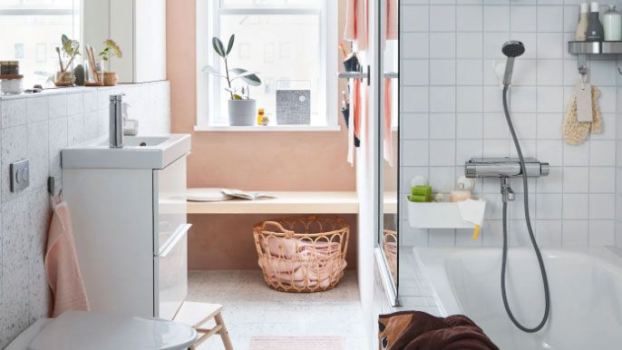 how to clean a bathroom: small pink and white bathroom with a shower over bath