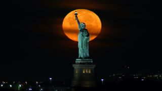 The almost-full Harvest Moon sets behind the Statue of Liberty before sunrise on Sept. 20, 2021