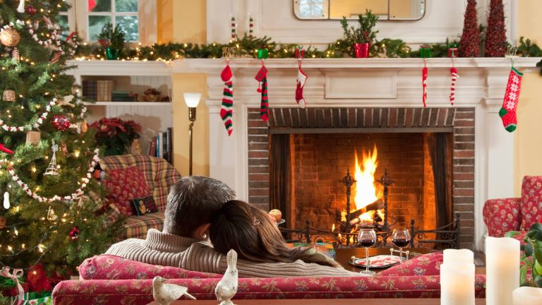 A man and woman sitting of sofa in front of lit fire at Christmas